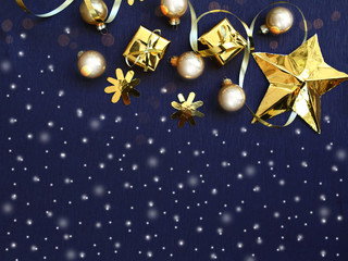 Merry Christmas and Happy New Year. Golden Christmas decorations and gift boxes on black background, flat lay photo, Xmas greeting card, banner, copy space for the text
