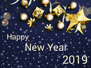Happy New Year 2019. Golden Christmas decorations and gift boxes on black background, flat lay photo, Xmas greeting card, banner