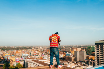 Man standing on the ledge of a building taking a picture