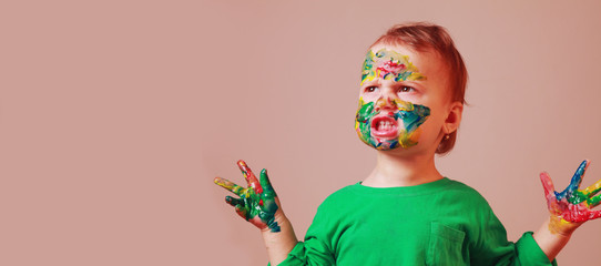 Children's makeup. Funny image of little cute child girl with a painted face. Humorous picture.