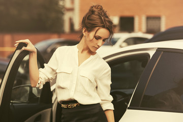 Young fashion business woman in white shirt getting out of her car