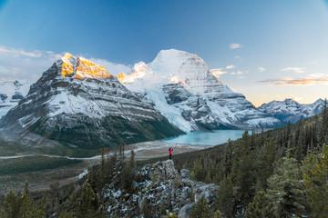 A lone person stands on a precipice