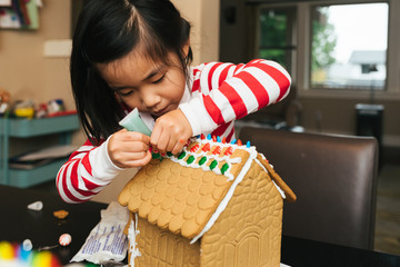 Young girl decorating a gingerbread house