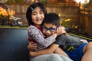Siblings hugging on a trampoline