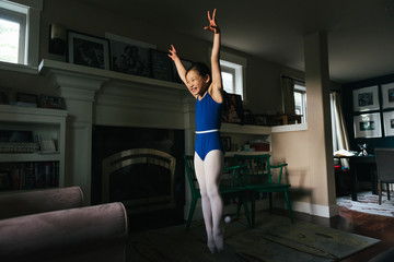 Young girl practicing gymnastics at home