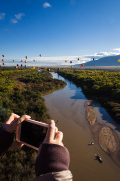 Person taking a picture of hot air balloons