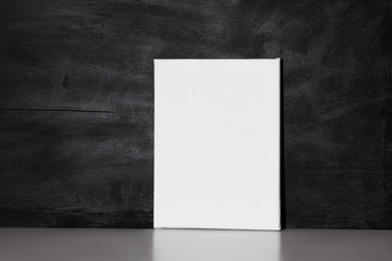 Blank canvas board and black wall. Mockup poster.