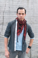Handsome trendy man in shirt and neck kerchief standing on street looking at camera