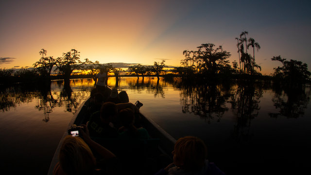 Tourists traveling by canoe on a lagoon in the Amazon while taking sunset photos