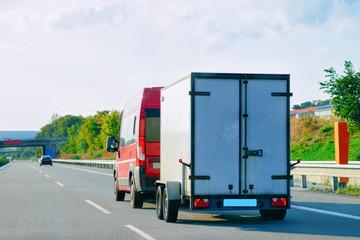 Mini van carrying trailer at asphalt road in Slovenia