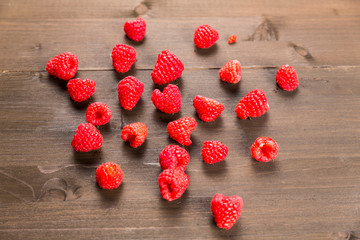 Red raspberries on a wooden background