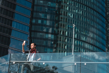 From below shot of stylish ethnic Latino man taking selfie on background of modern glass skyscraper in sunlight, Mexico city