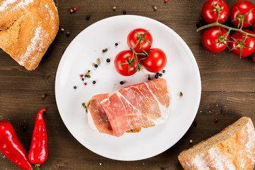 Slice of bread with preserved ham and ingredients. White plate on a wooden background