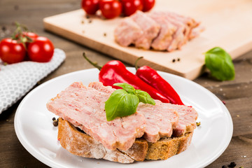 Slice of bread with preserved ham and peppers. White plate on a wooden background