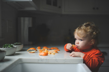 Cute baby girl eating orange while standing by kitchen counter at home