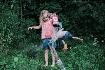 Full length of sister pouring water from rubber boot while brother amidst plants at park