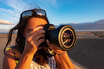 Closeup of a young caucasian female tourist taking pictures of landmarks in the desert at dusk