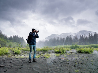 Male hiker photographing while standing on field against cloudy sky in Olympic National Park