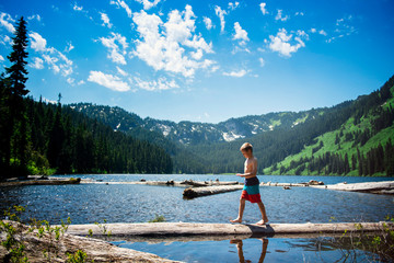 Side view of shirtless boy walking on log in lake against blue sky at forest
