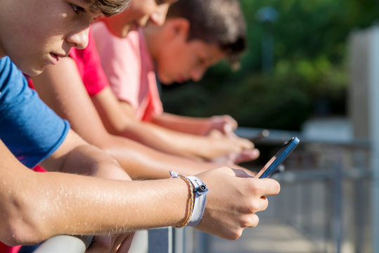 Side view of friends using smart phones while standing by railing during sunny day
