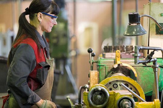 Metalwork industry. Factory woman turner working at workshop lathe machine