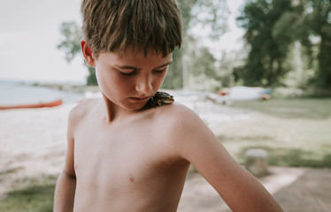 Close-up of shirtless boy looking at frog on shoulder while standing in forest