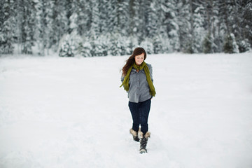 Smiling woman walking on snow covered field against pine trees in forest