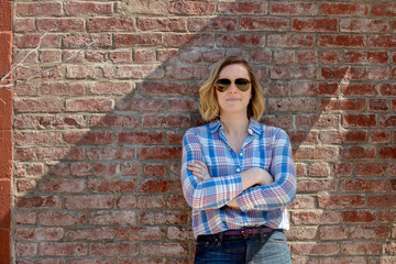 Portrait of confident female entrepreneur wearing sunglasses while standing by brick wall