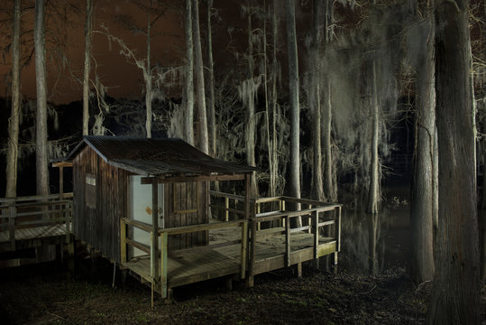 Wooden house by Caddo Lake in forest at night