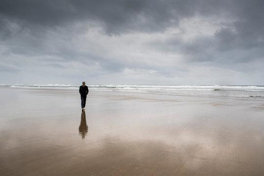 Man walking at beach against cloudy sky