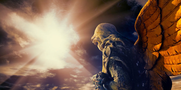 Antique statue of a guardian angel in sunlight.