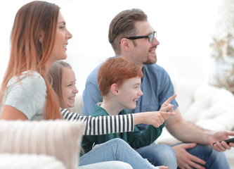 close up. the family watches their favorite show on TV