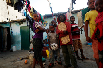 Children stand at the corridor of the house they share in Medina neighbourhood