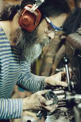 Side view of bearded engineer repairing lathe while standing in workshop