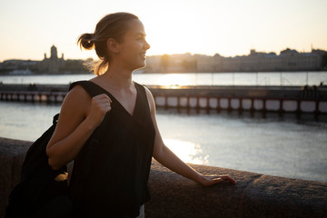 Smiling woman with backpack looking at view while standing by river in city during sunset