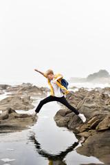 Boy jumping on rocks at beach against clear sky