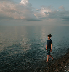 Boy walking at shore against sky during sunset