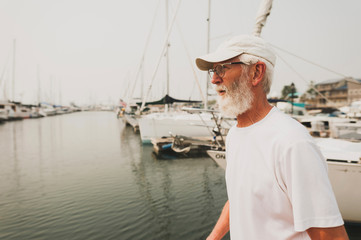 Side view of senior man looking away while standing at harbor against clear sky