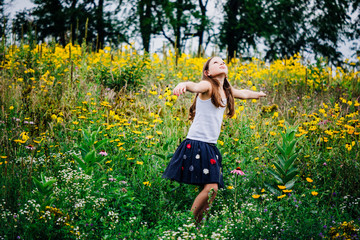 Girl with arms outstretched standing amidst plants at park
