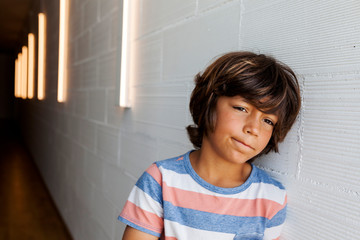 Bored thoughtful boy looking away while leaning by wall at home