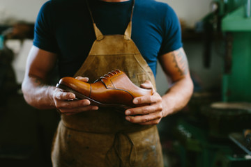 Midsection of shoemaker holding leather shoe while standing in workshop