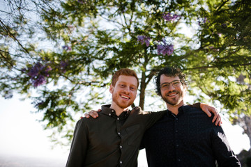 Low angle portrait of happy handsome brothers with arms around standing against trees at park