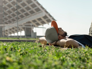 Surface level image of man with skateboard lying on grassy field against clear sky at park during sunny day