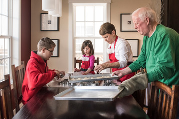 Grandchildren and grandparents making gingerbread cookies at home