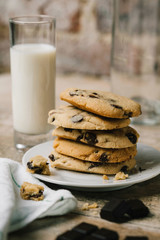 Close-up of stacked chocolate chip cookies in plate with milk on table