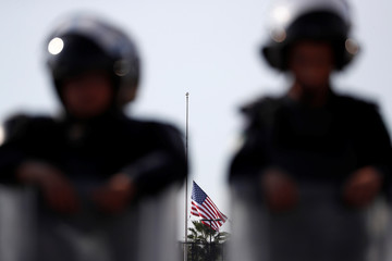 A U.S. flag is lowered in the U.S. Consulate as Mexican riot police officers stand guard outside during a demonstration by migrants, part of a caravan of thousands from Central America trying to reach the United States, in Tijuana