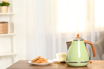 Stylish electrical kettle, cup and plate with cookies on table against blurred room interior. Space for text
