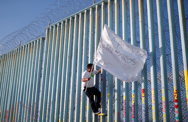 A migrant, part of a caravan of thousands from Central America trying to reach the United States, climbs the border fence between Mexico and the United States, in Tijuana,