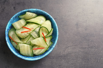 Dish with fresh cucumber salad on  table, top view. Space for text