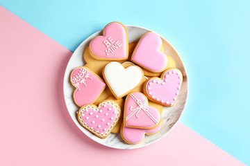 Plate with decorated heart shaped cookies on color background, top view